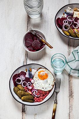 Labskaus, rollmops, pickled gherkin, beetroot salad, onion and fried egg - p300m1562479 by Susan Brooks-Dammann