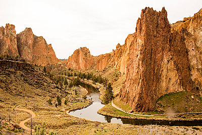 Stream through sheer cliffs in desert landscape, Smith Rock State Park, Oregon, United States - p555m1412143 by Adam Hester