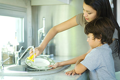 Mother and son washing dishes - p62310978f by Eric Audras
