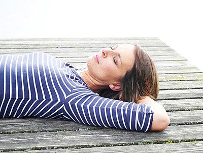 Frau liegt auf einem Steg  - p6430091 von senior images