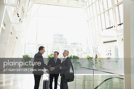 Businessmen handshaking in airport atrium