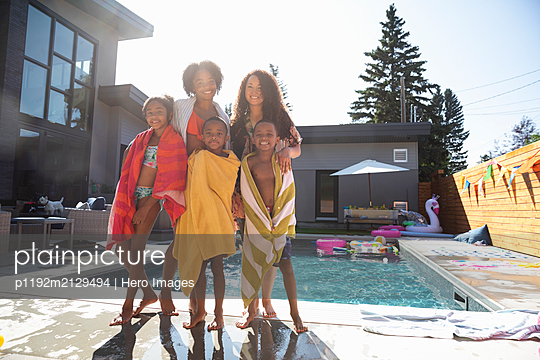 Portrait happy family at sunny, summer poolside - p1192m2129494 by Hero Images