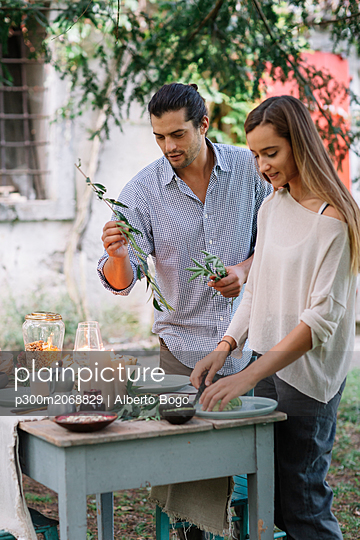 Couple preparing a romantic candelight meal outdoors - p300m2068829 von Alberto Bogo