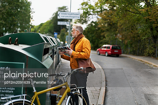 Man putting garbage into recycling bin - p312m2091639 by Pernille Tofte