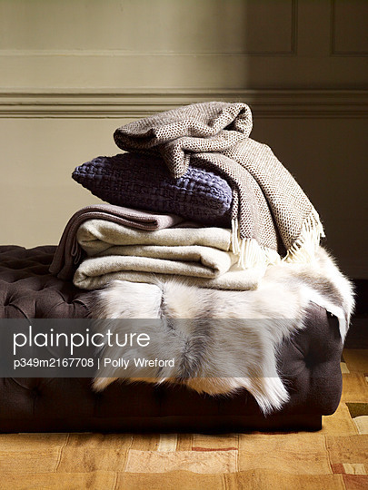 Folded woollen fabrics and fur rug on daybed. - p349m2167708 by Polly Wreford