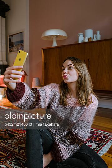 Junge Frau posiert mit Handy - p432m2148043 von mia takahara