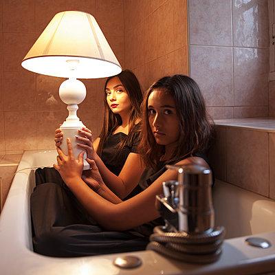 Zwei Frauen mit Lampe in der Badewanne - p1105m2133116 von Virginie Plauchut