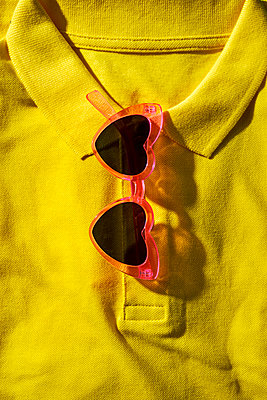 A pair of heart-shaped sunglasses on a folded yellow polo shirt - p1423m2215983 by JUAN MOYANO