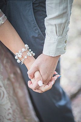 Close-up of bride and groom holding hands - p300m1204792 by Anke Scheibe
