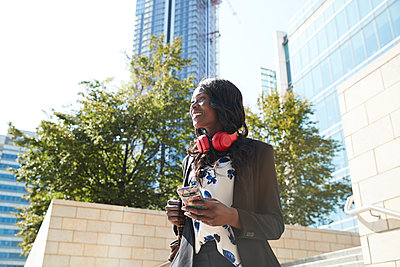 Smiling businesswoman with headphones and backpack using mobile phone while standing in city - p300m2241628 by Pete Muller