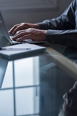 Male entrepreneur using laptop at home - p300m2276597 by Simona Pilolla