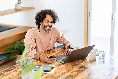 Male entrepreneur holding smart phone while working on laptop at home - p300m2276599 by Steve Brookland
