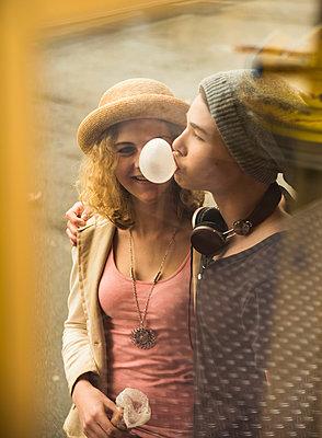 Teenage girl watching gum bubble of her boyfriend - p300m950835f by Uwe Umstätter