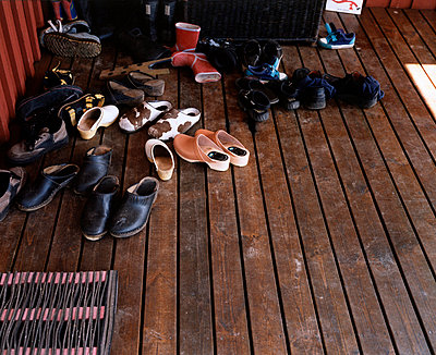 A collection of shoes on a porch - p3012778f by fStop