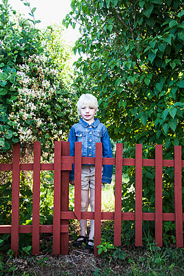 Young girl standing behind fence - p312m1121624f by Lina Karna Kippel