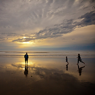A silhouetted family of three enjoy Rockaway Beach, Oregon. - p343m1168008 by Christopher Kimmel