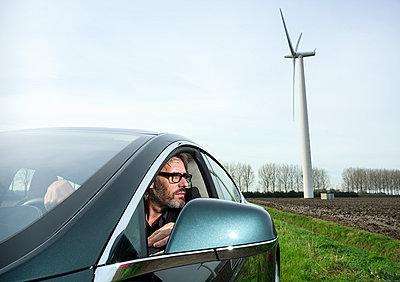 Man in car with wind turbine in background - p429m1006405f by Mischa Keijser