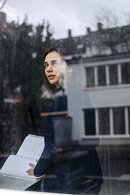 Geschäftsfrau blickt aus dem Fenster - p586m1510783 von Kniel Synnatzschke