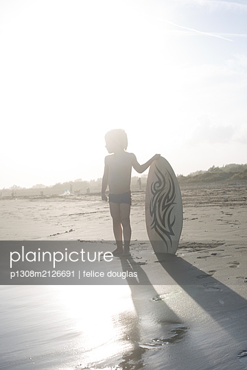 Kid with a skim board - p1308m2126691 by felice douglas