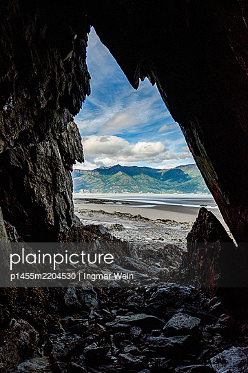 View from a cave onto shore and mountain range, Alaska - p1455m2204530 by Ingmar Wein