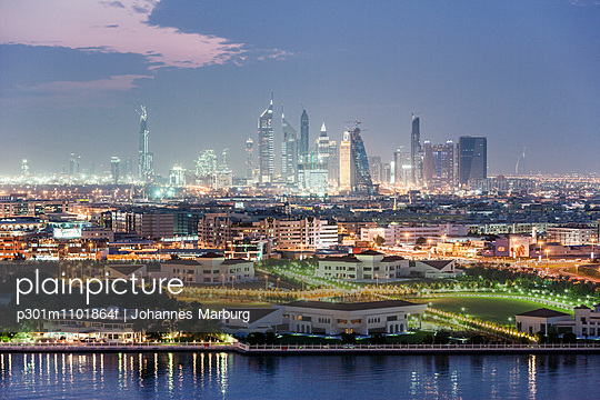 View of illuminated cityscape against sky at dusk - p301m1101864f by Johannes Marburg