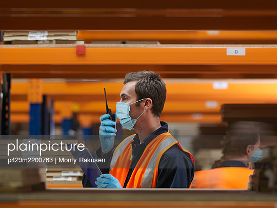 Man wearing surgical face mask and high visibility vest working in a large warehouse. - p429m2200783 by Monty Rakusen