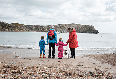 grandparents standing at the beach with grandchildren at lulworth cove - p1166m2107147 by Cavan Images