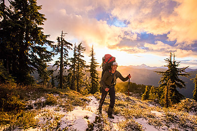 Backpacker hiking through forest at sunset. - p1166m2255885 by Cavan Images