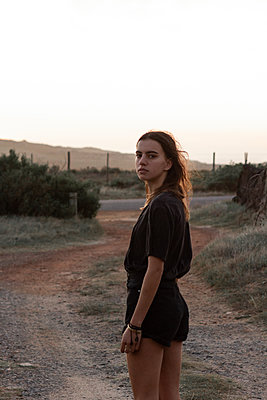 Teenage girl with long hair on a dirt road - p1640m2268666 by Holly & John