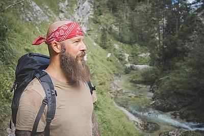 Mature man wearing bandana standing against trees in forest, Otschergraben, Austria - p300m2221406 by Epiximages