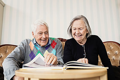 Happy senior couple reading book in living room at nursing home - p426m1131123f by Maskot