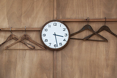 Wall clock and empty hangers on coat rack - p675m922951 by Marion Barat