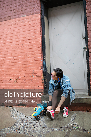 Cool young woman putting on roller skates in alley - p1192m2123454 by Hero Images