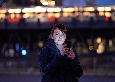 Frau mit Smartphone bei Nacht - p1124m1216815 von Willing-Holtz