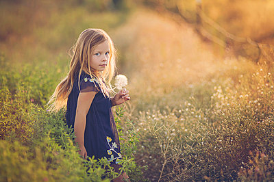 Side view portrait of girl holding dandelion while standing amidst plants on field during sunset - p1166m2024886 by Cavan Images