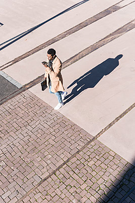 Businessman walking outdoors with briefcase, cell phone and earphones - p300m1568542 by Uwe Umstätter