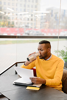 Man drinking hot drink from reusable cup while reading documents in a cafe - p300m2155286 by Hernandez and Sorokina