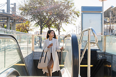 Young woman with smartphone leaving subway station - p300m2166213 by VITTA GALLERY