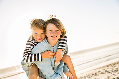 Portrait of boy carrying brother piggyback on the beach - p300m2167044 by Floco Images