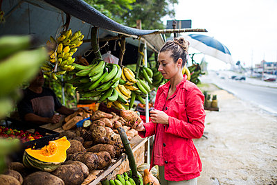 A young woman shops at a fruit stand on the roadside of a small Puerto Rico village. - p343m1218054 by Michael Hanson