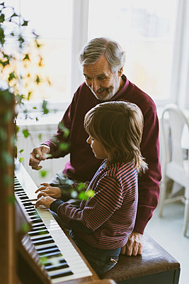 Happy senior man talking to great grandfather playing piano at home - p426m1468221 by Maskot