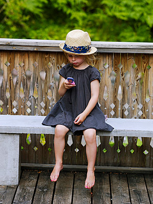 Girl wearing straw hat sitting on bench with toy phone - p528m716635 by Anna Kern