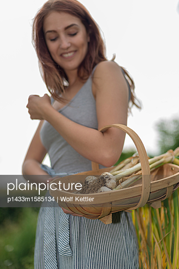 Young woman carrying a trug with freshly harvested garlic - p1433m1585134 by Wolf Kettler