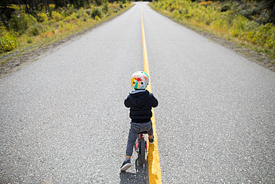 Rear view of young boy biking on paved roadway. - p1166m2153330 by Cavan Images