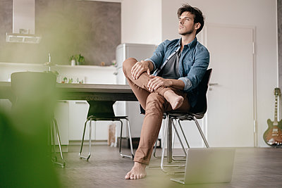 Pensive young man sitting in a loft - p300m1549417 by Kniel Synnatzschke