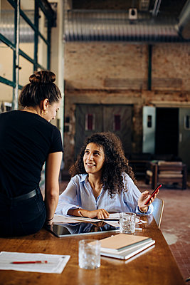 Two young businesswomen with smartphone in loft office - p300m2144825 by Sofie Delauw
