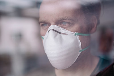 Portrait of man wearing protective mask behind windowpane - p300m2171046 by Joseffson