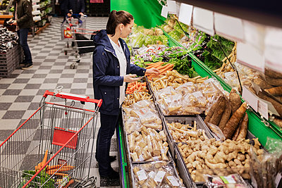 High angle view of woman holding phone while buying groceries in supermarket - p426m1148165 by Maskot