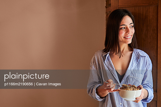 Young woman having breakfast next to a window at home. Copyspace - p1166m2190656 by Cavan Images