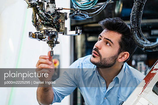 Male entrepreneur concentrating while analyzing robotic arm in manufacturing factory - p300m2225295 by Daniel Ingold